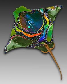Eagle Ray by Karen Ehart. Art glass wall art. Rivers of dichroic glass are layered with mosaic-like chips of colorful iridized and dichroic glass, all flowing across this fused and slumped glass wall sculpture highlighted with gold pen work. This piece includes a cast and welded bronze tail and hanger for display. No two pieces are alike; each is unique and will vary. Find it at www.artfulhome.com