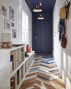 deco couloir avec peinture bleu canard, porte et plafnd en bleu canard, parquet disposé de manière asymétrique peint en bleu, blanc et gris, patère sur le mur en blanc, cases blanches comme espaces de rangement, luminaire blanc et bronze, cinq tableaux avec des cadres blancs, deux luminaires en couleur bronze