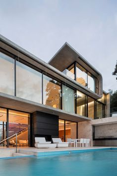 Multiple levels are tucked between curved concrete to create various platforms for living in this house.