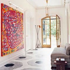 A painting by Yayoi Kusama commands a wall in the entrance hall of @sarastorydesign's restored Victorian house perched above the Hudson. Photo by @francoisdischinger