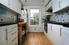 white cabinets, black worktop, floorboards