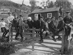 Tolv småländska barn sitter på en grind. Kanske väntar de på en grindslant? 1920-tal. Fotograf: Gustav Heurlin
