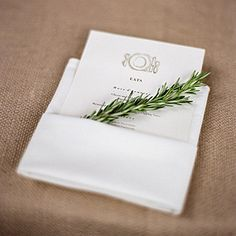 At the wedding reception, tucked into a napkin, a menu card and a sprig of rosemary rested at each place setting.