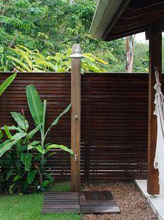 Casa de praia. Jardim com gramado, deck e pedriscos. Chuveiro e torneira embutidos em coluna de madeira. Paisagismo