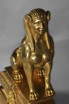 Detail of an antique firedog with sphinges decoration in golden bronze, 19th century