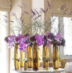 jarrones ambar con orquideas lilas y plumas