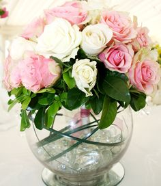 white and pink roses in a bouquet, resting in a fish-bowl vase