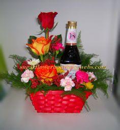 Arreglo floral con una botella de vino.