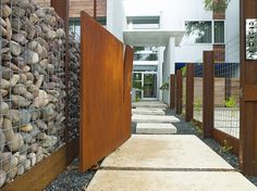 Weekly Faves: 5 Inspiring Outdoor Spaces Designer George Sacaris created this unusual entry wall with boulders and wire. An oxidized iron door creates an impressive entrance to this modern home. Gabion Cages, Gabion Wall, Outdoor Spaces, Outdoor Living, Entry Wall, Modern Fence, Landscape Walls, Iron Doors, Garden Fencing