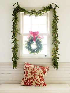 keeping holiday decor simple is as easy as a swaged garland + wreath suspended with ribbon in front of a window