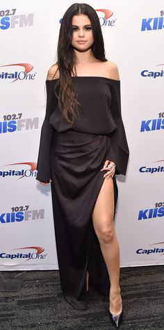 Selena Gomez gave the cold-shoulder silhouette the holiday treatment, arriving at the KIIS FM Jingle Ball Concert in a sexy bell-sleeved off-shoulder top and matching high-slit skirt, both by Camilla and Marc, complete with Dauphin jewelry and black pumps.