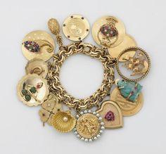 A fourteen karat gold charm bracelet suspending fifteen gem-set gold charms mounted in fourteen and eighteen karat gold; gross weight approximately: 194.6 grams...   Sold for US$ 4,880