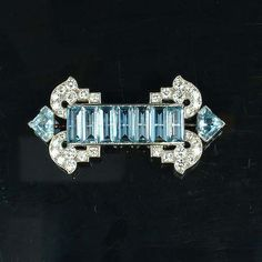 An art deco aquamarine and diamond brooch, by Cartier, circa 1935, set with a central line of seven uniform rectangular step-cut aquamarines, terminating with a scrolling brilliant-cut diamond spray to each corner and a single mitre-shaped aquamarine, signed Cartier London and numbered, length 5.2cm.