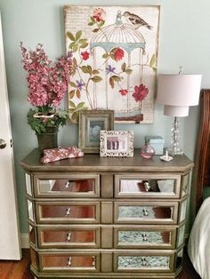 Mirrored Chest and whimsical artwork from HomeGoods keep this guestroom lighthearted. #homegoodshappy #guestrooms #walldecor