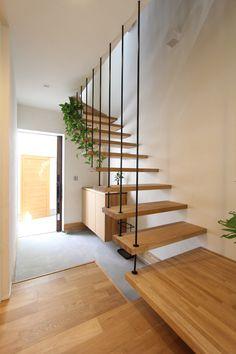 土間で仕上げた玄関は造り付けのシューズボックスや、開放的な吊り階段が印象的な空間です。階段下は自転車やベビーカーも置けるスペースとして活用できます。吊り階段のアイアンに植栽をコーディネートすることで、日常に視覚的変化をもたらします。 Tiled Staircase, Interior Staircase, Staircase Remodel, Staircase Design, House Roof Design, Small House Interior Design, Wooden Cottage, House Stairs, Modern Farmhouse Decor
