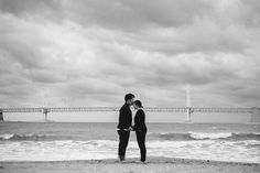 JINHO + ANNE COUPLE SHOOT - A kiss beneath the bridge! An overcast day can produce beautiful light for an engagement shoot! Take this session for instance! For more photos of this overcast beach engagement photo shoot, click the link above!  // Aaron and Jillian Photography - destination Wedding Photographer based in downtown Charleston, SC //