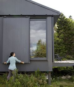 A Tiny Cabin is This Writer's Off the Grid Getaway - Photo 14 of 20 - When Alex or Bruce leave the island, closing up shop is as simple as sliding panels of corrugated metal into place to protect the windows.