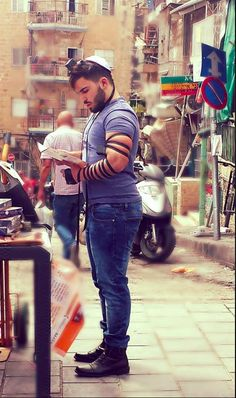 """girlactionfigure:  """"I took this great pic of a friend in the chabad tefillin booth in the shook. It was crazy busy Friday afternoon with tons of noise, smells, people, and not an inch of space but he never once broke his concentration as he talked to God.Source: Dina VinitskyHumans of Judaism"""