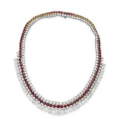 A RUBY AND DIAMOND NECKLACE  The front suspending a graduated oval-cut diamond fringe, joined by circular-cut diamonds to the circular-cut ruby and diamond two row neckchain, mounted in 18k gold and platinum, 17 ins. Christie's Price $99.750