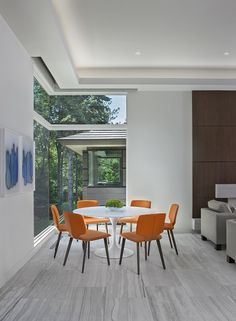It's Personal Design | Michigan Design Center - The contemporary orange dining chairs add a pop of color to this classic Knoll tulip table.