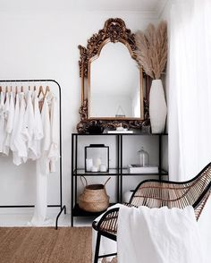 Love this minimalist space with white walls and an ornate mirror.
