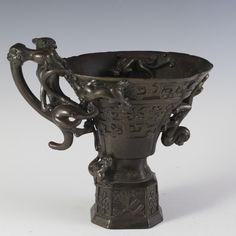 DESCRIPTION:Chinese bronze vessel embellished with an array of foo lions along the front and foo lion handles intertwined with one another,…