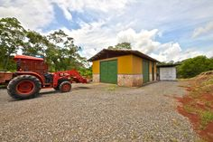 Property includes barn/shed and Kubota tractor w/ 11 attachments. Container in background is workshop equipped with water & electric and also stays on the property along with cement mixer and other equipment.