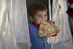 A Syrian Kurdish refugee child from the Kobani area eats bread at a refugee camp in Suru