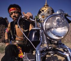 Jimi Hendrix posing for a shot aboard his Harley Davidson in the desert…with Kaiser helmet and flowers!