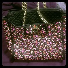 Betsey Johnson purse Betsey Johnson bag only used a couple of times. Quilted with hearts with a pink and red floral pattern. Gold chain straps and gold hardware on bow with floral liner. Dimensions 16 x 5 1/2 x 13 Betsey Johnson Bags Shoulder Bags