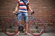 Close-up of guy with bicycle against brick wall Stock Photo