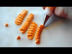 Making ruffles with royal icing.      www.alibeesbakeshop.com  facebook: Ali Bee's Bake Shop  Twiter: AliBeesBakeShop  email: alibeesbakeshop@gmail.com    Tools Used:    Tip #103  Thick Consistency Royal Icing  Americolor Orange