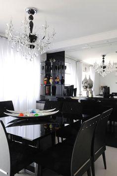 Na sala de jantar, a mesa de tampo preto de vidro serigrafado com base de inox e o jogo de cadeiras na mesma cor traduzem elegância.