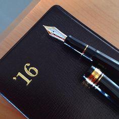 投稿続き。 カスタム845、モンブラン146とだいたい同じ体格だけどペン先が更にシュッと長めな分、紙当たりが柔らかい。 金銀染分けのペン先も良い。キャップにURUSHIって金文字で小さく書いてあってそこがまた可愛い。 そして能率手帳ゴールドに負けないおじさま具合... アサヒヤ紙文具店の赤漆バージョンと迷った時があったけど(いつかフォルカンで欲しいけど...)この黒金軸、好き。 #万年筆 #能率手帳 #能率手帳ゴールド