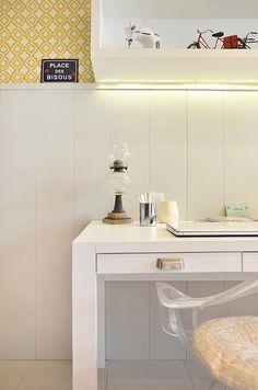 Cantinho de trabalho. Uma mesa com lindo puxador com design diferente. Cadeira em acrílico com almofada em amarelo que super combina com o papel de parede.