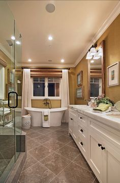 The master bathroom is elegant but not too serious. Color and texture is added with the green grasscloth wallpaper