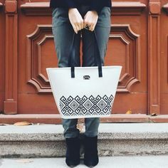 White leather bag with black embroidery.