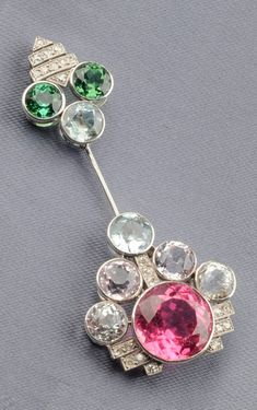An Art Deco Platinum, Gem-set, and Diamond Jabot, France, bezel-set with pink and green tourmaline, kunzite, colourless spodumene, green beryl, and aquamarine, old mine and old European-cut diamond melee highlights, lg. 2 1/2 in., French guarantee stamps.
