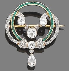 An emerald and diamond brooch, circa 1910 -  Designed as a millegrain-set old brilliant and rose-cut diamond swirl, surrounding a calibré-cut emerald circlet, suspending at its centre a millegrain-set old brilliant-cut diamond swag centre and at its base a collet-set pear-shaped diamond drop, mounted in silver and gold, diamonds approx. 1.80ct. total, length 3.3cm