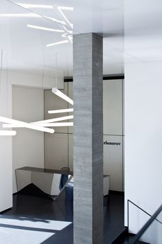 Pitsou Kedem has added perforated aluminium screens, concrete panels and a glossy ceiling to a sales office in Tel Aviv