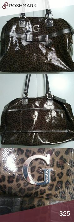 """EUC-GUESS BAG EUC-HUGE GUESS BAG! leopard print with darker bow decoration where the G is in front. Lots of room in this big bag! Measures approximately 20 1/2"""" Wide and 12 1/2"""" Long x 9"""". Small scratches on the the metal buttons on bottom and a small hardly visible scratch as shown in the last photo of bottom. GUESS Bags"""