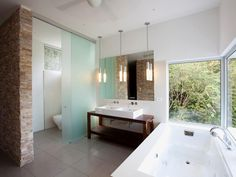 Torcida, located in the Osa Peninsula in Costa Rica, uses rich woods and a soft palette in the bathroom, reflecting the abundant flora and fauna native to the property. A frosted glass divider separates the toilet from the rest of the space, which features a jetted tub and an open wood vanity with double sinks.