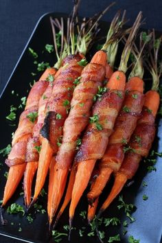Bacon Wrapped Maple Glazed Carrots are the perfect side dish to any holiday meal! Carrots wrapped in bacon and covered with a sweet and spicy glaze!