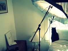 paint the inside of an umbrella with white spray paint and attach lamp.. instant reflective umbrella?