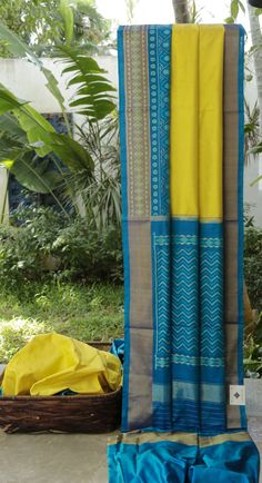 This bright Ikat silk sari has a lemon yellow coloured body. The border and pallu are in cerulean blue with different patterns in Aegean blue, pearl white thread work and gold zari making it a grac…