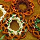 3/4 CUP CHOCOLATE CHIPS;70 MINI PRETZELS, DECORATIONS.  MELT CHOCOLATE OVER LOW HEAT. PLACE 5 PRETZELS IN A CIRCLE, WITH THE END THAT HAS 1 HOLE ON OUTSIDE OF RING, ONTO A COOKIE SHEET WITH WAX PAPER.   TAKE 1 PRETZEL AT A TIME, DIP THE SIDE HALFWAY INTO THE CHOCOLATE,  PLACING THEM BACK INTO CIRCLE.  FORM A SECOND LAYER. PLACE THEM OVER THE NEWLY FORMED WREATH, SO THAT COATED HOLES OVERLAP. DECORATE WITH TOPPINGS, WHILE THE COATING IS STILL SOFT.  REFRIGERATE FOR 15 MINS. YIELDS 7 WREATHS