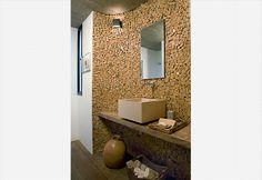 O amplo mosaico de pedras portuguesas se impõe no lavabo desta casa. A arquiteta Flavia Petrossi fez a escolha inspirada na atmosfera anos 1970 da casa. A execução não é complicada: o cimento foi aplicado no painel de 1,60 x 2,25 m e recebeu as pedras, sem rejunte