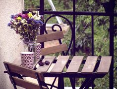Wildflower balcony with plums & candles Wooden chairs & table On a rainy summer's afternoon