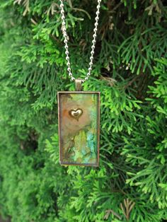 A forest of greens and browns and a gold heart necklace -Resin Jewelry Pendant -Three Demensional wearable art by Terripoppinscrafts. $18.00, via Etsy.