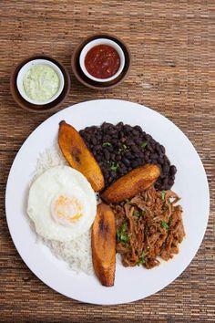 """Pabellón Criollo, uno de los platos típicos de la gastronomía venezolana. Incluye caraotas (frijoles) negras, arroz blanco, tajadas fritas de plátano y carne """"mechada"""". Algunas variantes, como la de la foto, incluyen un huevo frito"""